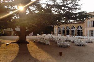 Salle de réception de mariage en extérieur. Le soleil passe dans un arbre.